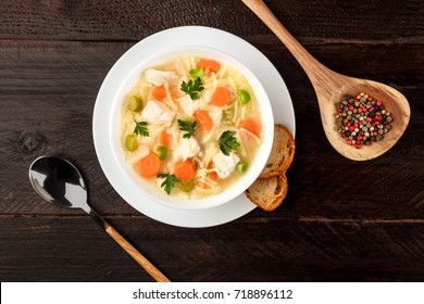 An overhead photo of a plate of chicken and noodles soup, shot from above on a dark rustic texture with a spoon, a wooden ladle with peppercorns, slices of bread, and a place for text