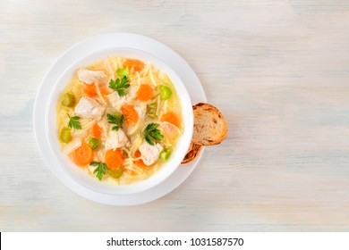 An overhead photo of a plate of chicken, vegetables, and noodles soup, shot from above on a light wooden texture with slices of bread and a place for text