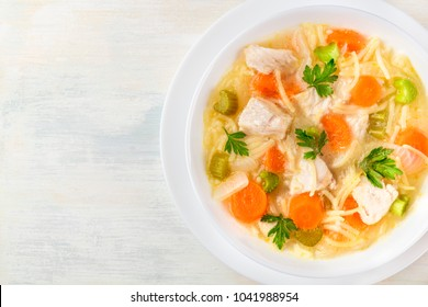 An overhead photo of a plate of chicken, vegetables, and noodles soup, shot from above on a light wooden texture with a place for text