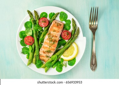 An overhead photo of a plate of grilled salmon with green asparagus, cherry tomatoes, corn salad, and a slice of lemon, a healthy diet dish with a place for text