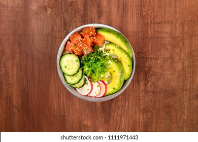 An overhead photo of poke, traditional Hawaiian raw fish salad, with wakame, sea vegetable, cucumber, radish, avocado, with copy space