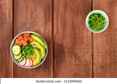An overhead photo of poke, traditional Hawaiian raw fish salad, with a bowl of wakame, sea vegetable, and copy space