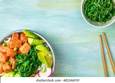 An overhead photo of poke, traditional Hawaiian raw fish salad, with a plate of wakame, sea vegetable, with chopsticks and copy space. Selective focus