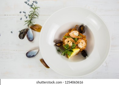 An overhead photo of a seafood risotto on teal textures, with a fork and a spoon, a glass of white wine, and a place for text