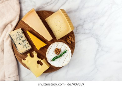 An overhead photo of a selection of cheeses, shot from above on a white marble table, with a place for text