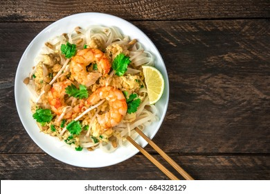 An overhead photo of a Shrimp Pad Thai, traditional Thai dish with stir fried rice noodles, shot from above on a rustic texture with chopsticks and copy space
