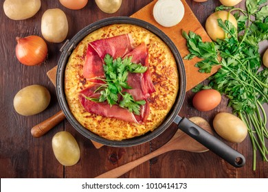An overhead photo of a Spanish tortilla in the traditional frying pan, with jamon and parsley, on dark rustic textures with ingredients and a place for text