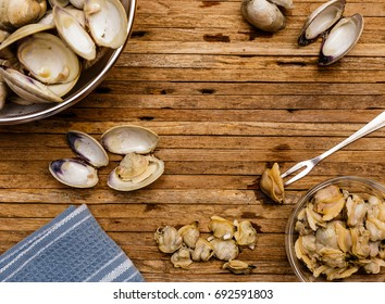 Overhead photo of steamed little neck clams being shelled on cutting board.  Blue towel, empty clam shells and clam meat can be seen in photo.
