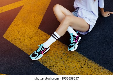 Overhead photo of tanned caucasian girl chilling in city after training. Magnificent woman wears white socks and colored shoes sitting on street. Beautiful sexy girl with long legs in jeans short.