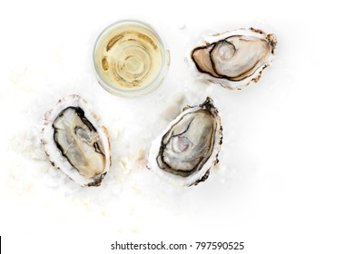 An overhead photo of three freshly opened oysters on ice, with a glass of wine, and a place for text