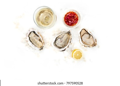 An overhead photo of three freshly opened oysters on ice, with a glass of wine, lemon, the typical vinaigrette sauce, and a place for text
