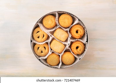 An overhead photo of a tin can of Danish butter cookies, shot from above on a light background texture with a place for text