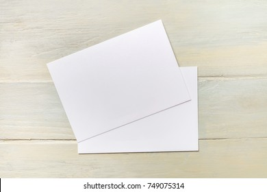 An overhead photo of two blank cards, shot from above on a light wooden texture with a place for text, a design template for an invitation or like