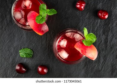 An overhead photo of two vibrant red drinks with cherries, fruit, and mint on black