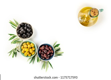 An overhead photo of various olives in bowls with leaves and a cruet of olive oil, with copy space, on a white background