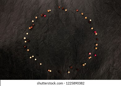 An overhead photo of various peppercorns, shot from the top on a black background forming a frame for copy space