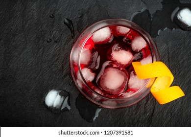 An overhead photo of a vibrant cocktail with campari and an orange twist garnish, shot from the top, with ice cubes on a black background, with copy space