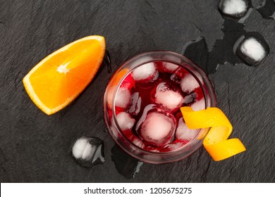 An overhead photo of a vibrant Negroni cocktail with campari and an orange twist garnish, with an orange slice, shot from the top, with ice cubes on a black background, with a place for text