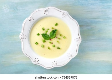 An overhead photo of vichyssoise, a French potato and leeks soup, with chopped green onions, pink peppercorns, and mint leaves for decoration, on a teal background with a place for text