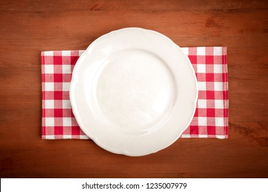 An overhead photo of a white plate on a gingham cloth on a dark rustic wooden background with copy space