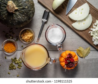Overhead photograph of the ingredients of homemade pumpkin soup including onion, turmeric, coconut cream, kabocha pumpkin, and minced garlic