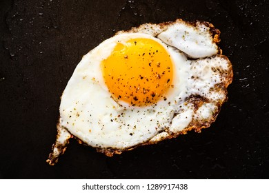 An overhead photograph of a single fried egg, sunny side up cooked in a frying pan.  Ground pepper coving the egg and yellow egg yoke.