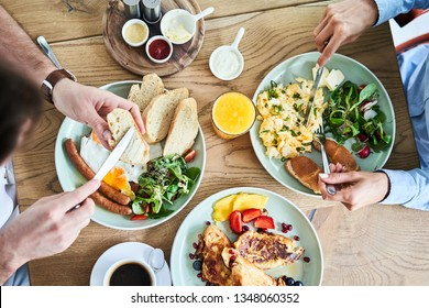 Overhead picture of couple eating tasty breakfast at restaurant.
