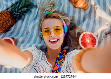 Overhead portrait of excited girl in white outfit resting on towel, having fun, spending great time . Tropical fruits, pineapple. Boho accessories.  Yellow sunglasses.