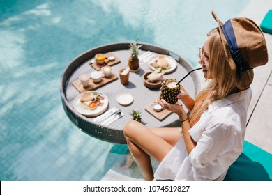 Overhead portrait of smiling blonde woman in brown hat drinking cocktail in pool. Outdoor shot of excited female model chilling at resort with fruits.
