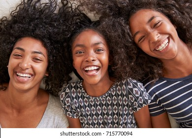 Overhead Portrait Of Three Teenage Sisters Lying On Bed At Home
