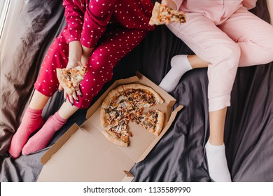 Overhead portrait of two girls in pajamas sitting on bed with italian fast food. Lazy female models eating pizza on dark sheet.