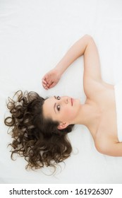 Overhead portrait of a young brunette lying in bed at home