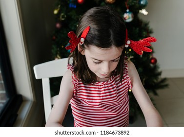 Overhead portrait of a young girl wearing novelty Christmas reindeer antler clips in her hair, sitting in front of a Christmas tree