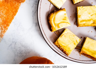 Overhead of pumpkin cheesecake bars on a serving platter on white marble surface with orange pumpkin linen.