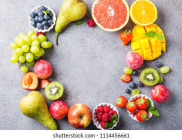 Overhead shoot with fresh assorted fruits and berries on light gray background. Colorful clean and healthy eating. Detox food. Copy space. Top view.