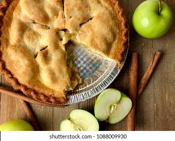 Overhead shot of an apple pie on a rustic wood surface