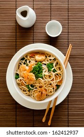Overhead shot of Asian noodles with broccoli and sesame shrimp.