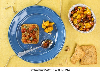 Overhead shot of baked tomato with toast on blue plate with yellow backgorund