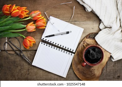 Overhead shot a bouquet of an open book or garden planner, glasses, coffee, sissors and flowers over a wood table top ready to plan an agenda. Flat lay top view style.