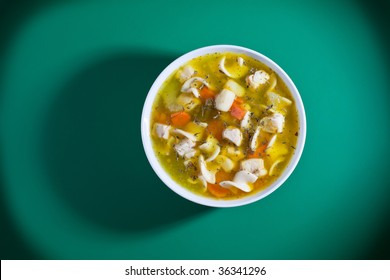 Overhead shot of bowl of soup on green table
