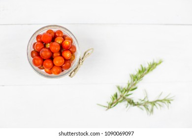 Overhead shot of cherry tomato in bowl with rosemary on white wooden table