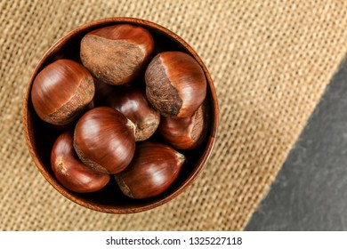 Overhead shot - chestnuts in small wooden bowl on jute tablecloth