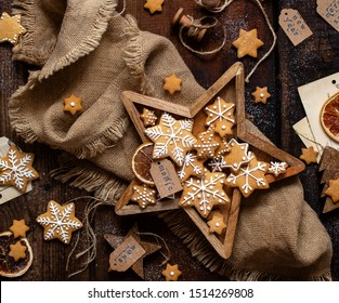 overhead shot of christmas snowflakes shaped cookies with beautiful icing decoration in wooden star shaped box stands on rustic brown table with sackcloth