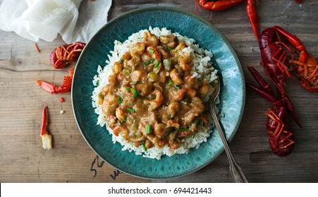 Overhead shot of crawfish étouffée over rice on a turquoise blue plate.