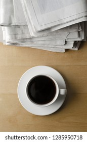 Overhead shot of a cup of black coffee with saucer on light wood laminate table with stack of newspapers.