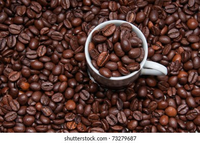 Overhead shot of a cup filled with roasted coffeee beans surrounded by more roasted beans
