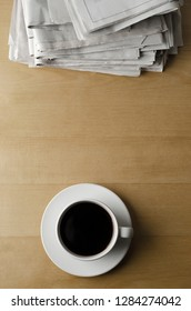 Overhead shot of a cup and saucer of black coffee placed on a light wood laminate table with a pile of newspapers.