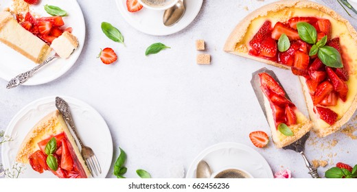 Overhead shot of cups of coffee, delicious homemade strawberry cheesecake and flowers on light gray background. Top view, flat lay. Copy space.