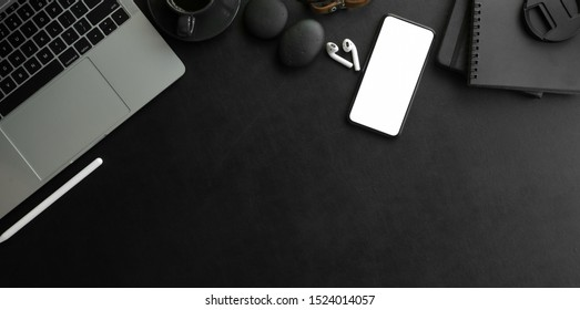 Overhead shot of dark modern workplace  with laptop computer and office supplies with copy space