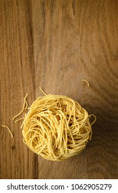 Overhead shot of egg noodles nest stack on wooden surface with broken noodle fragments scattered below. Copy space above.